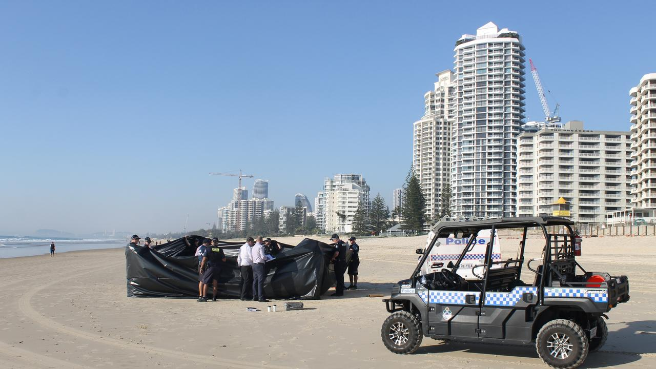 A black sheet was propped up to conceal the body of a man found on the beach at Surfers Paradise. Picture: Luke Mortimer