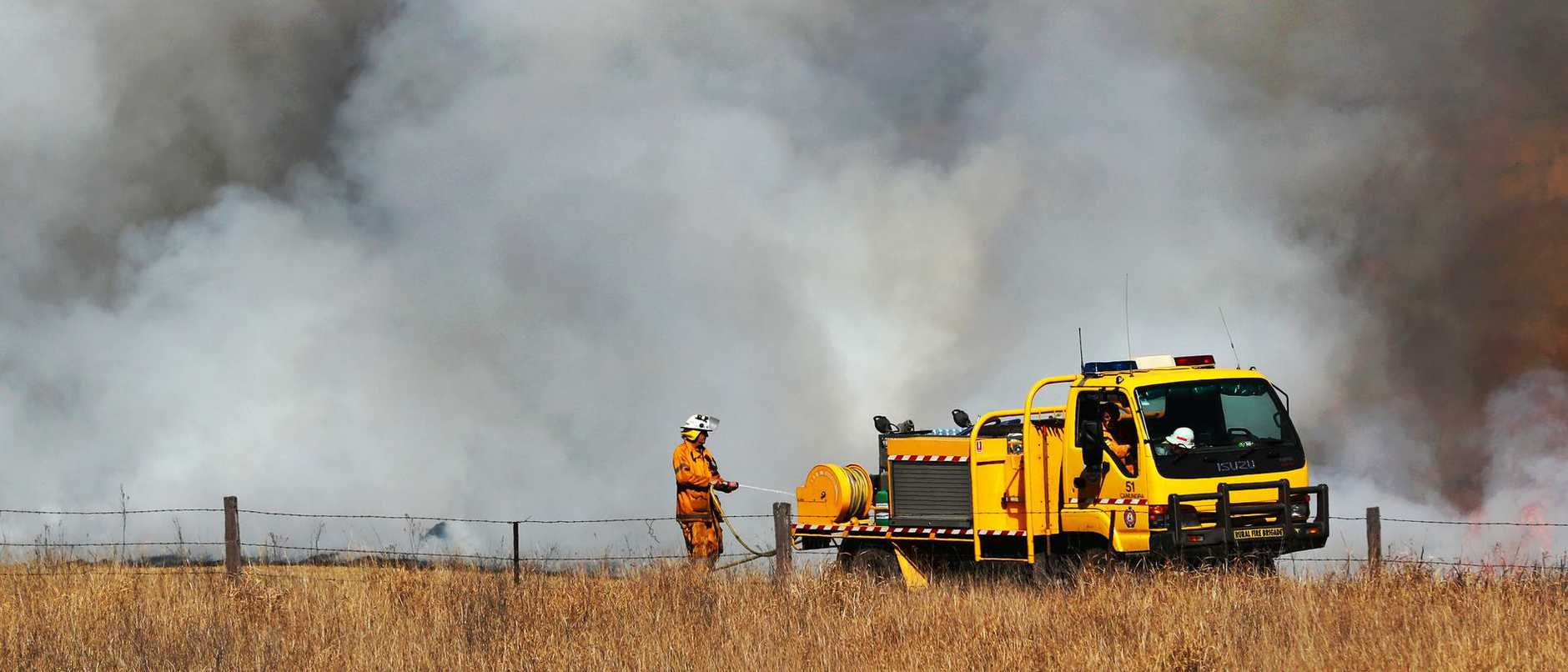 Firefighters battle in the Gold Coast hinterland yesterday. Picture: Nigel Hallett