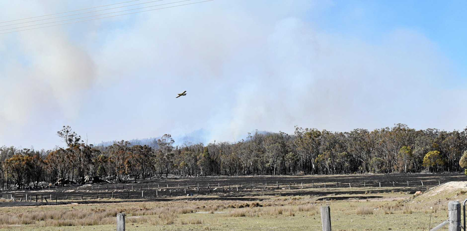 Planes fly over dropping water on fires in the Amiens and Applethorpe area.