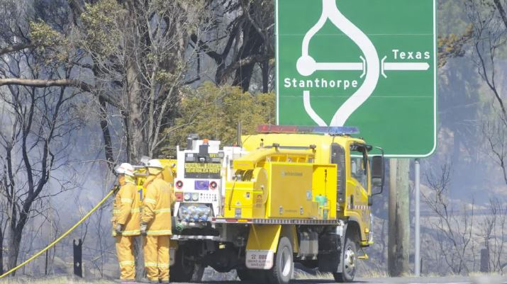 Rural firefighters dousing grass fires at the northern end of Stanthorpe on the New England Highway.