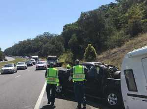 Car towing caravan rolls on Bruce Hwy