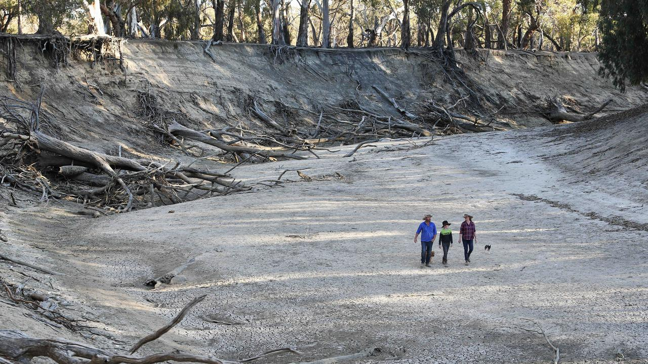 The Smith family: Wayne and wife Arleta with son Jud, 10, in the dry river bed of the Darling River that runs through their Karoola Station. Picture: Rohan Kelly