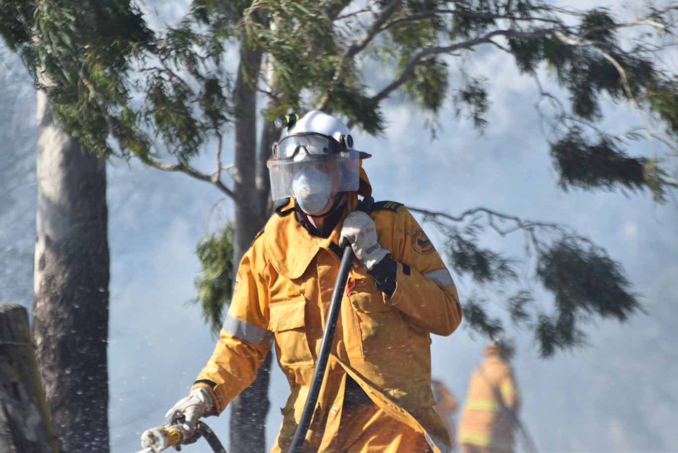 A firefighter extinguishes a fire which started on Spencer St, Gatton.