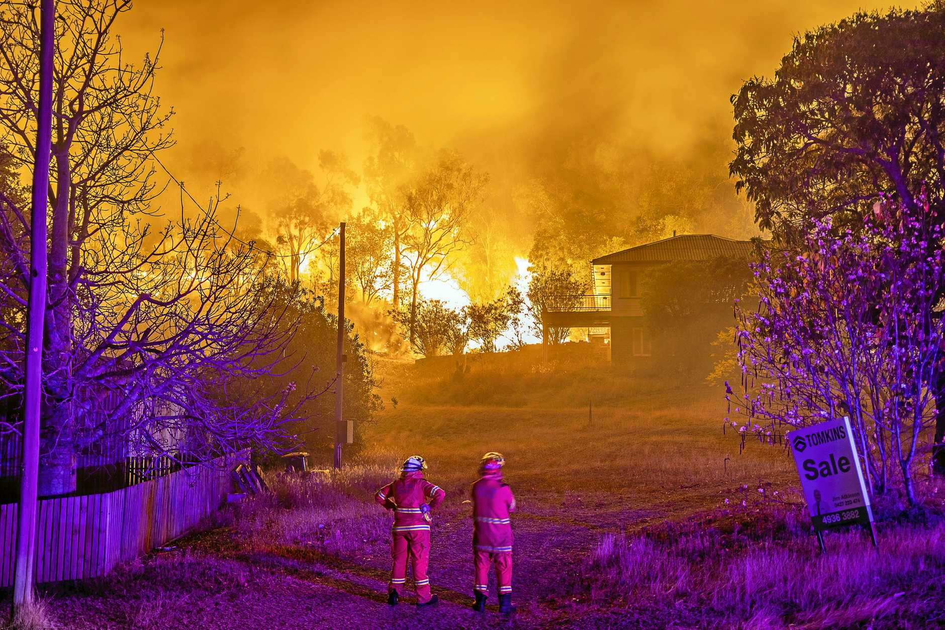 HARD WORKERS: Firefighters work to keep a bushfire away from houses.