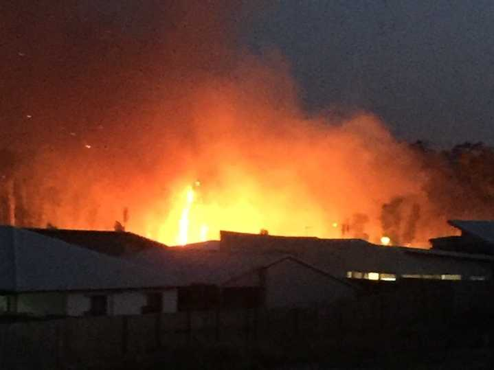 Flames burn within metres of homes at Peregian Springs.