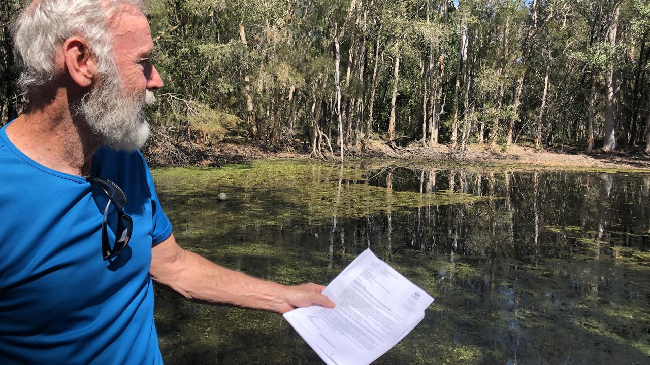 Cornubia resident Russell De Leacy at his pond, which council sprayed with a herbicide at a cost of $200. PHOTO: JUDITH KERR