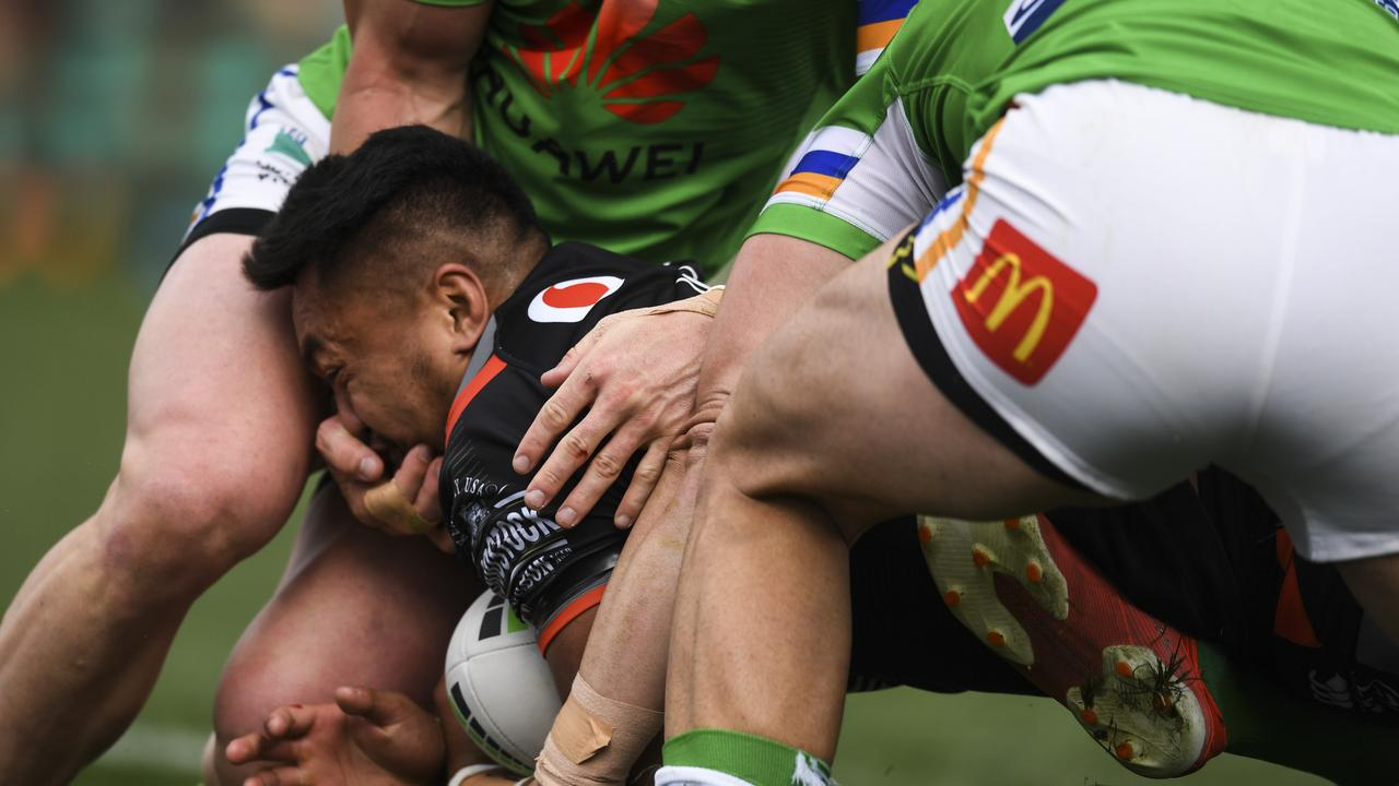 Hudson Young has his hand in the face of Adam Pompey. Photo: AAP Image/Lukas Coch