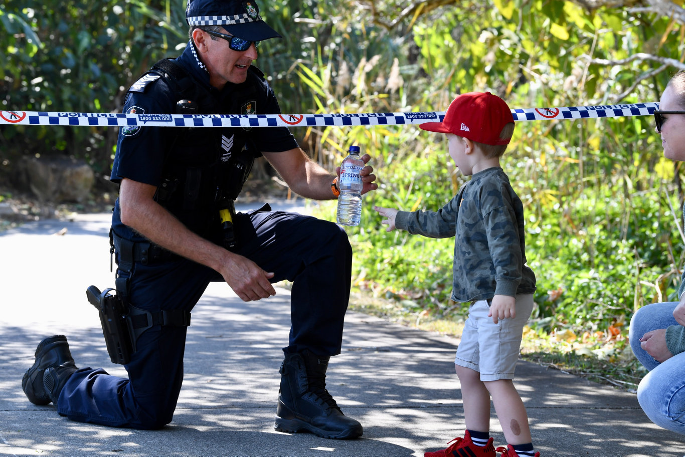 J.J Kelly,3, from Caloundra hands out a bottle of water to Sgt. Phillip Stevens on duty at the Peregian fires. Photo: Warren Lynam