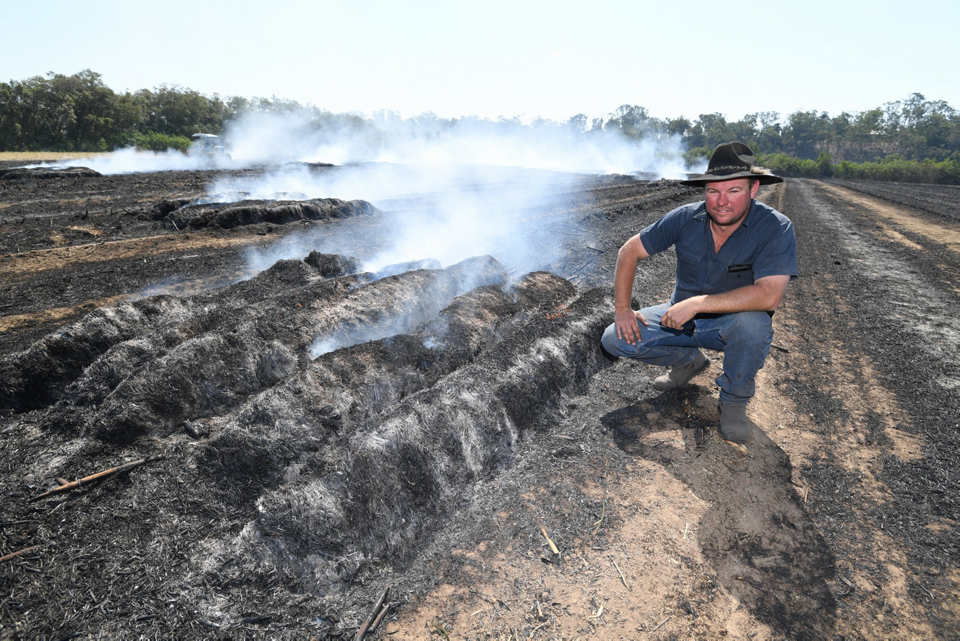 Walkers Point cane farmer Nathan Doyle with the remains of 500 bales of cane mulch that went up in smoke when 15 acres of cane paddock caught fire.