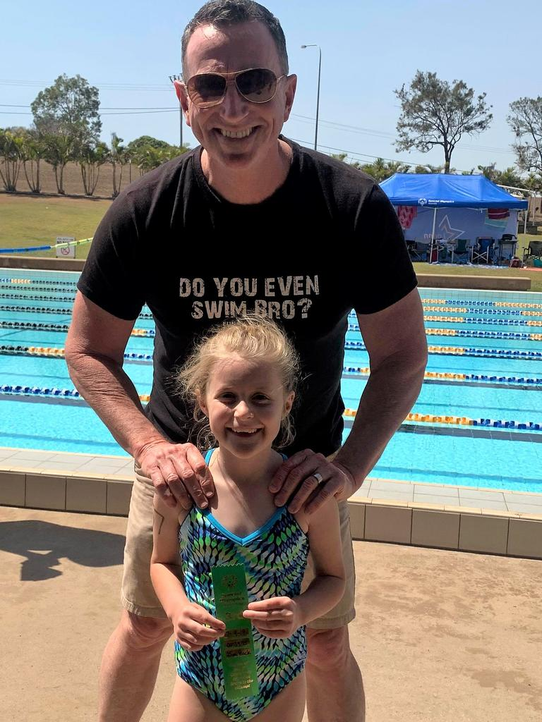 In her first ever swimming carnival, Isla Williams (7) receives her ribbon from former Olympian Duncan Armstrong.
