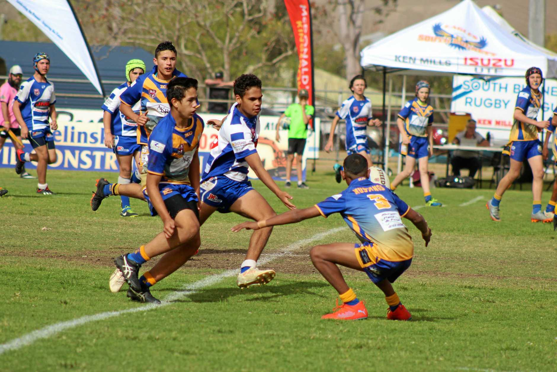 Dominique Sandow trying to defend the ball against Murgon Mustang players at the grand final.