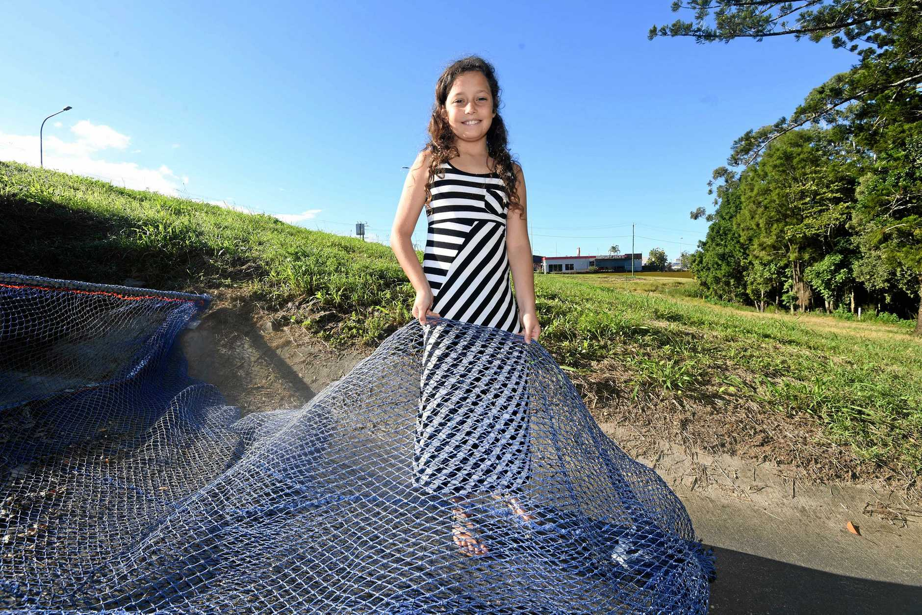 Atua Bentley of Cooloola Cove helps demonstrate the cleaner oceans drain filter developed by her father, Paul Bentley and road tested by Gympie Regional Council.