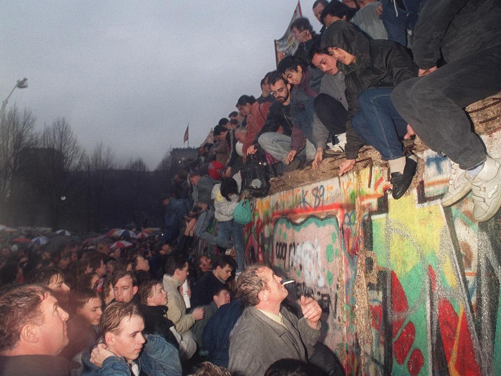 People from East Germany greet citizens of West Germany at the Brandenburg Gate in Berlin, 22 December 1989. The significance of the fall of the Berlin Wall gave the 1990s an undeniable air of optimism.