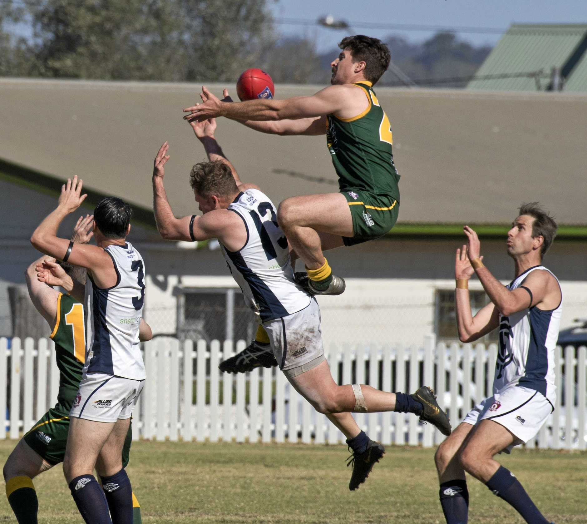 Goondiwindi's Angus Croft gets up high on the back of Coolaroo's Josh Stahlut during the Allied Pickfords Cup grand final.