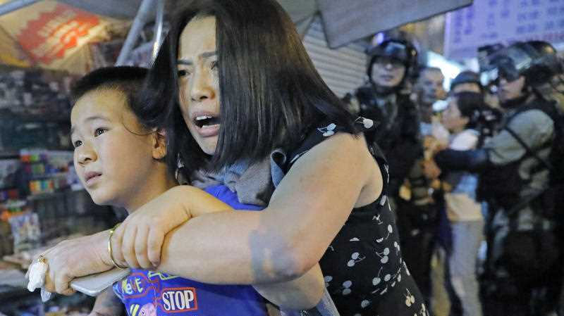 Mother and son leave as police arrive after pro-China supporters confronted with journalists in north point, at a local market of Hong Kong, Sunday, Sept. 15, 2019.