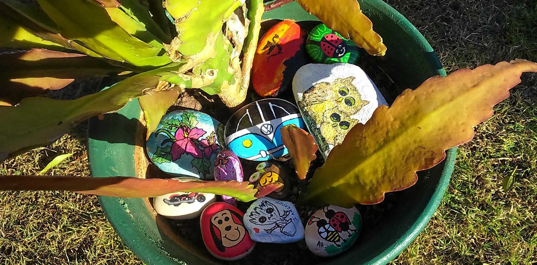 Using painted rocks and pebbles are not only pretty, they are a practical mulch.