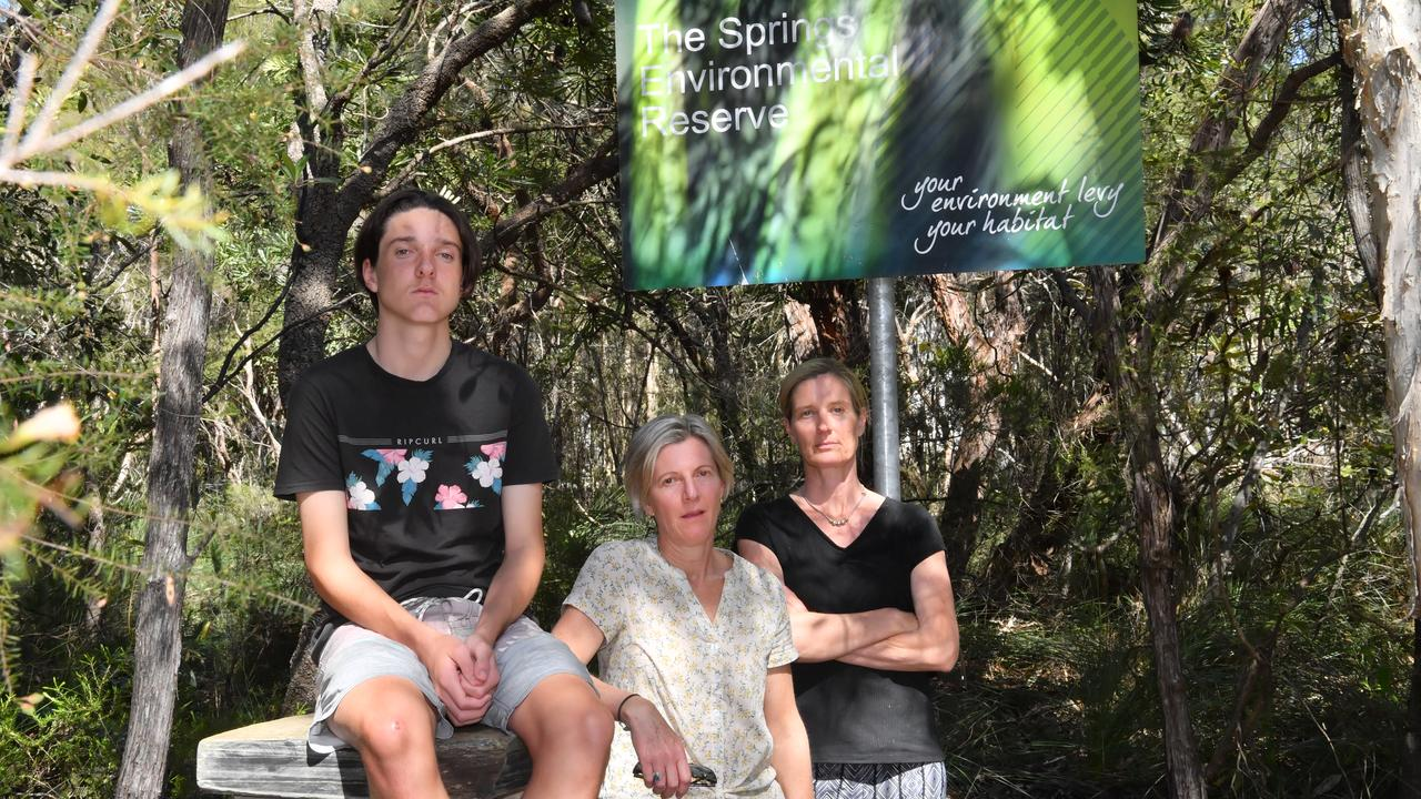 Lisa and Ben Lindsay and Louise Quilty with The Springs Environment Reserve sign near their homes. Photo: John McCutcheon