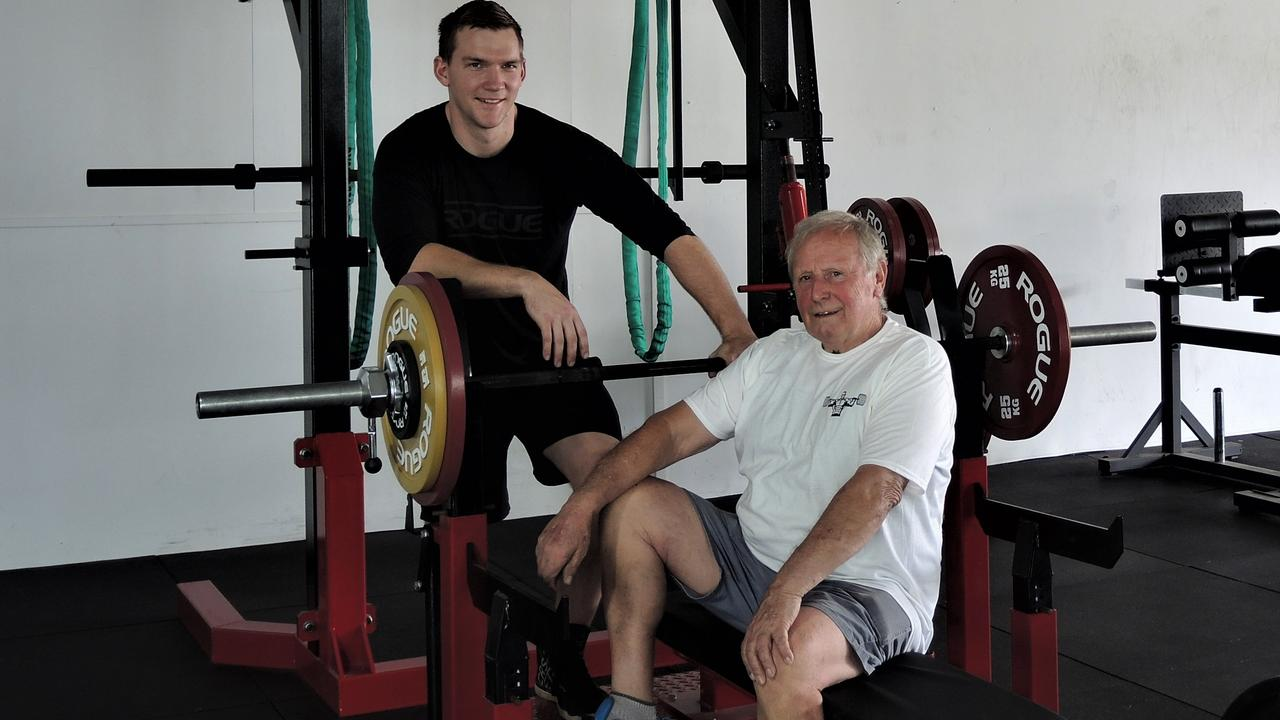 Strength coach Peter Cox prepares John Dellow for his world champion bench press lift. Picture: Contributed