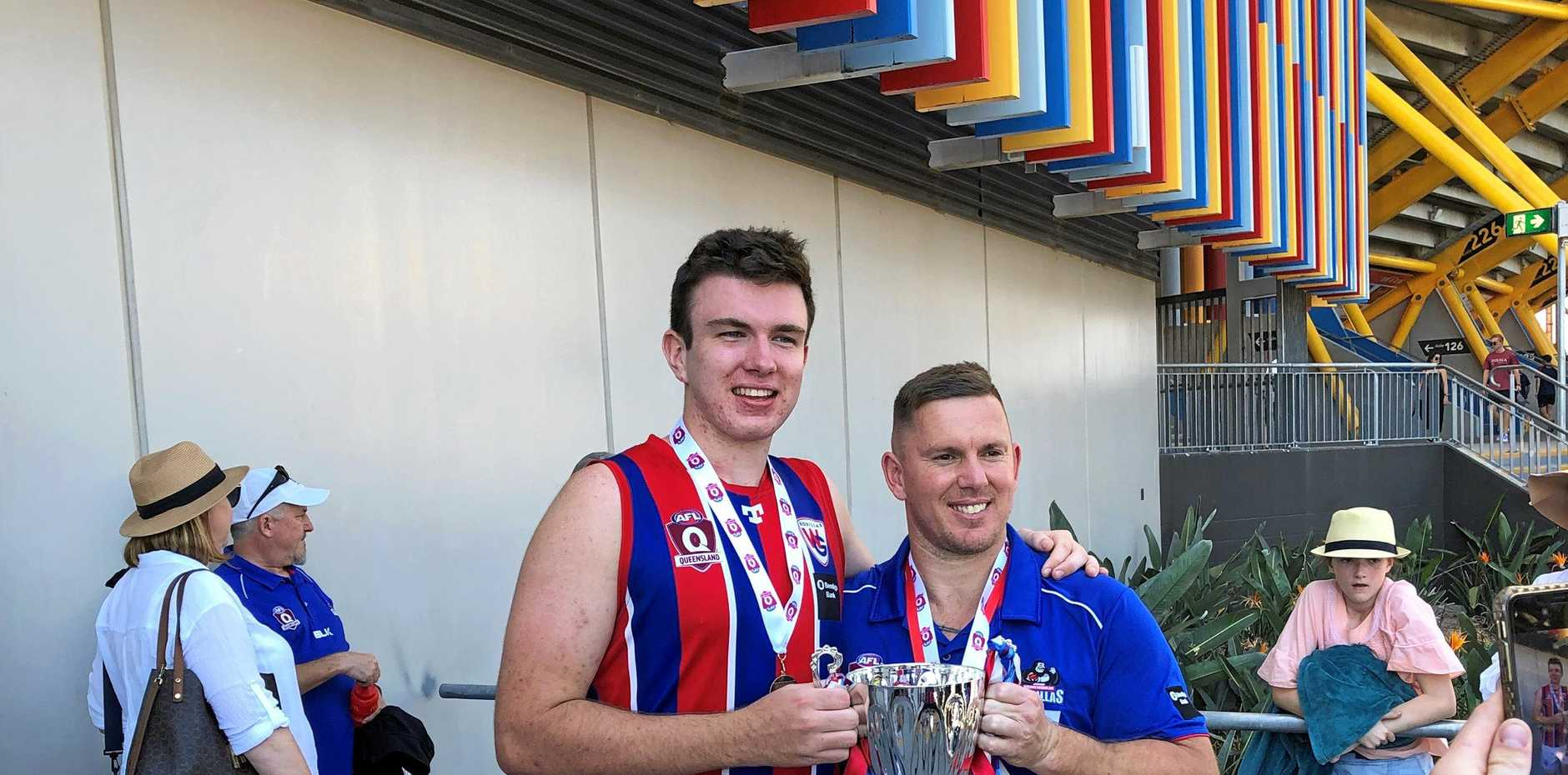 VICTORY: Winning QAFL colts player and former Scots PGC student Harry Keenan with his coach and former AFL player Brent Maloney after a premiership win.
