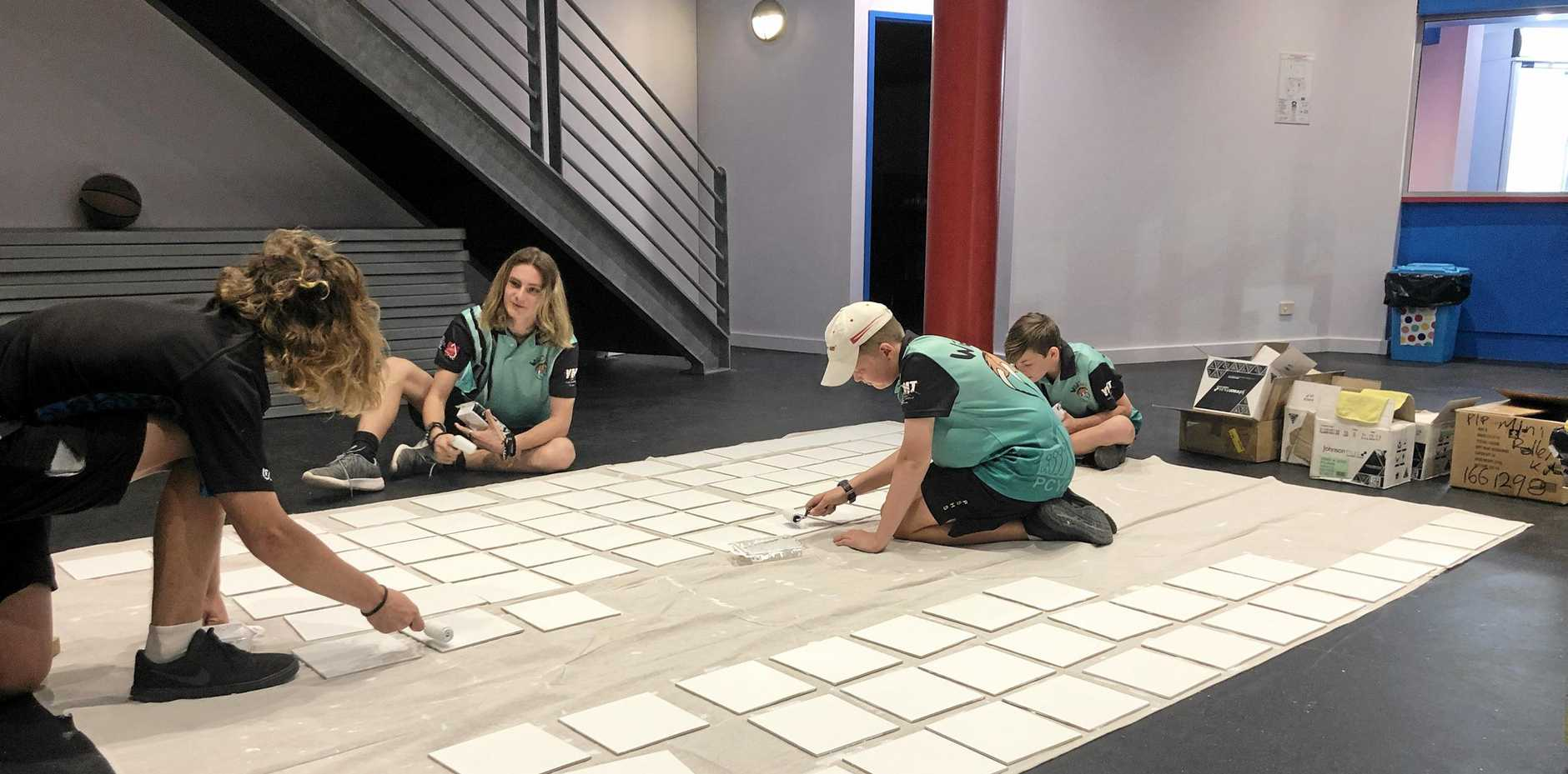 LENDING A HAND: Whitsunday PCYC youth team members Riley Petterson, Rhett Hill, Jesse Frisch and Phoenix Hill help prepare tiles for the PCYC Helping Hands wall.