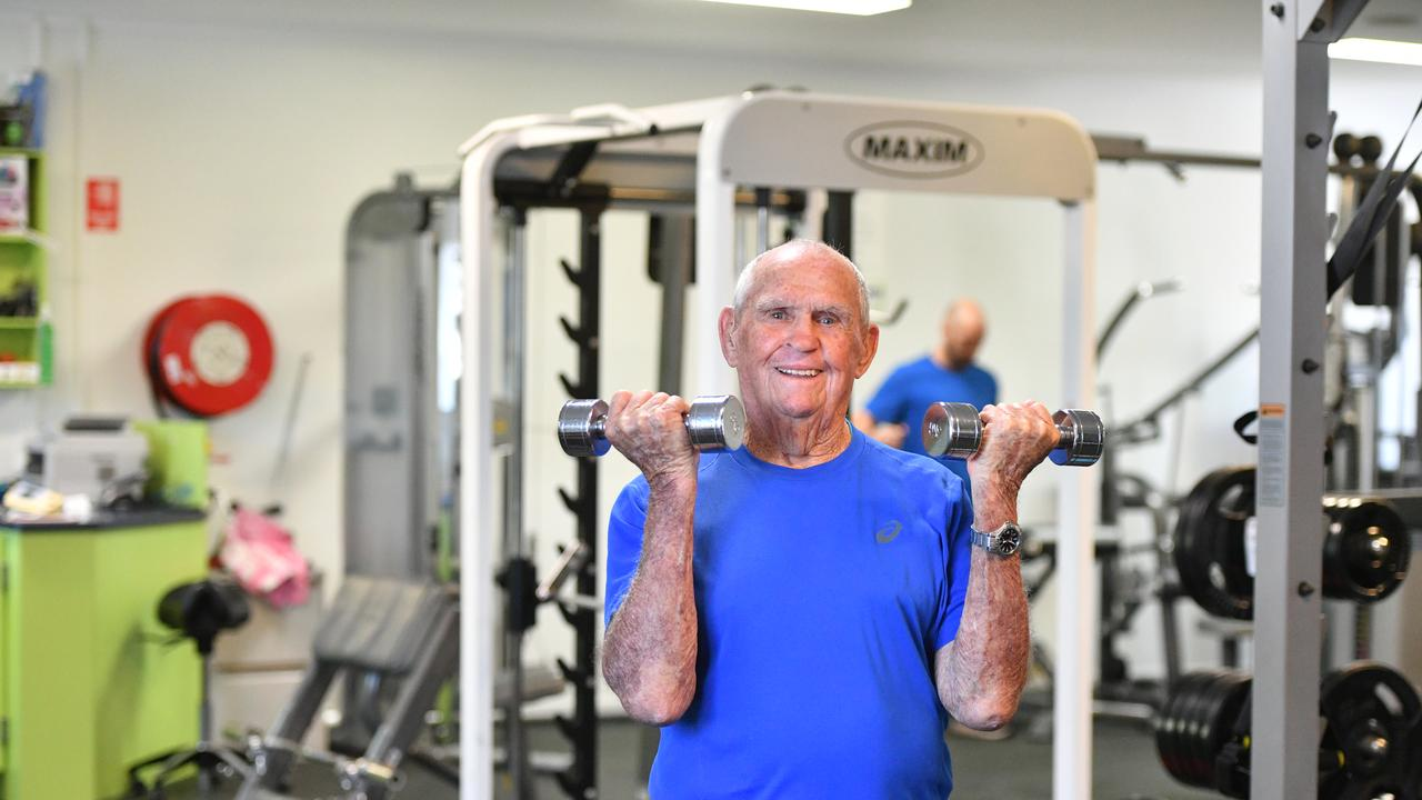 Lewis Weston, 90, lifting weights and doing a bicep curl at the Gladstone Physio & Fitness gym