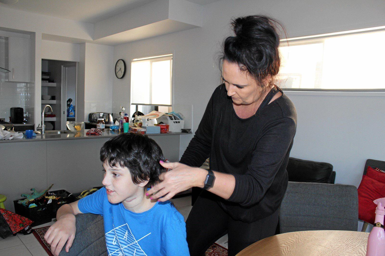 ESSENTIAL SERVICE: Giggles and Scissors founder Pam Waring-Baker with client Doug, 11, who is  autistic and epileptic.
