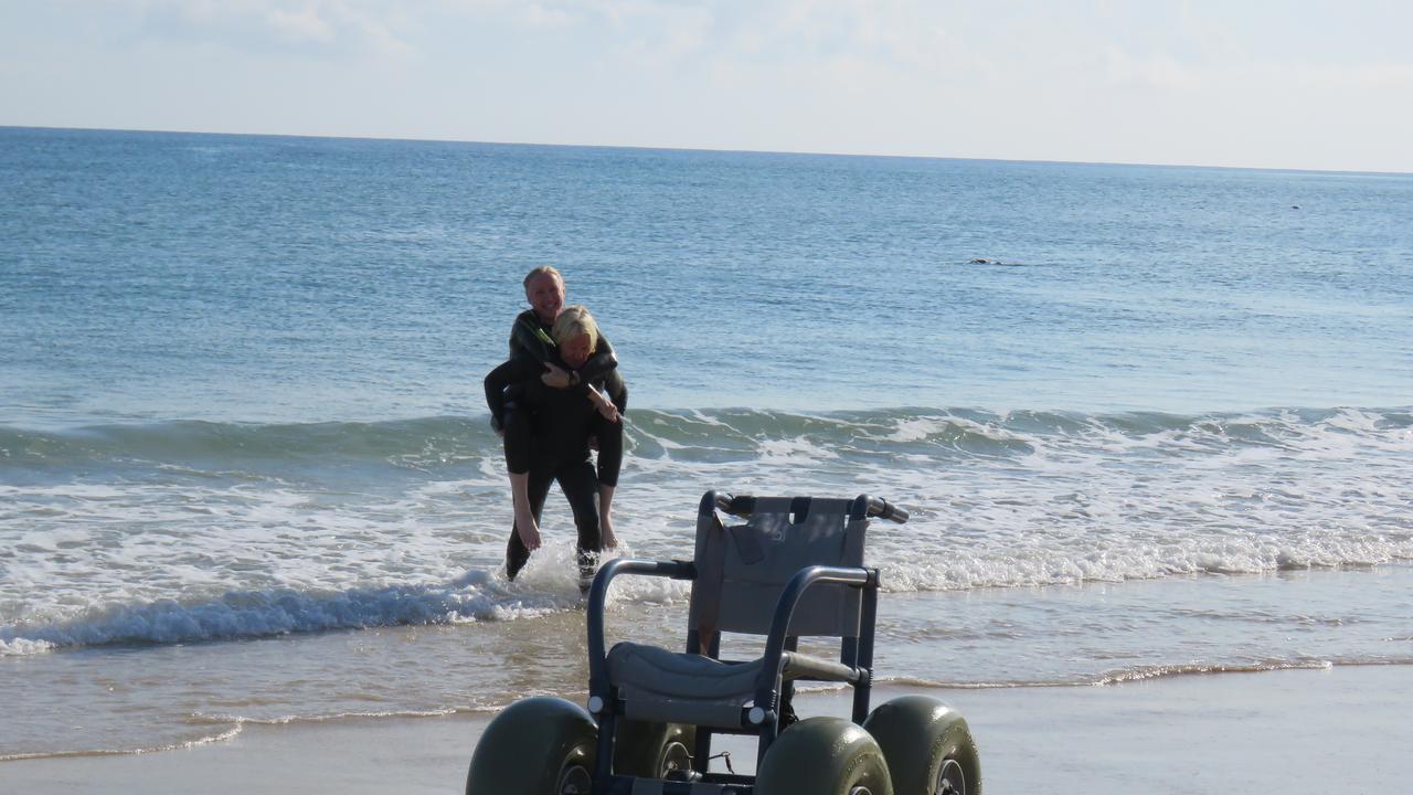Julie Hollowell piggy-backs Anne-Marie Howarth from the water on Noosa Main Beach.