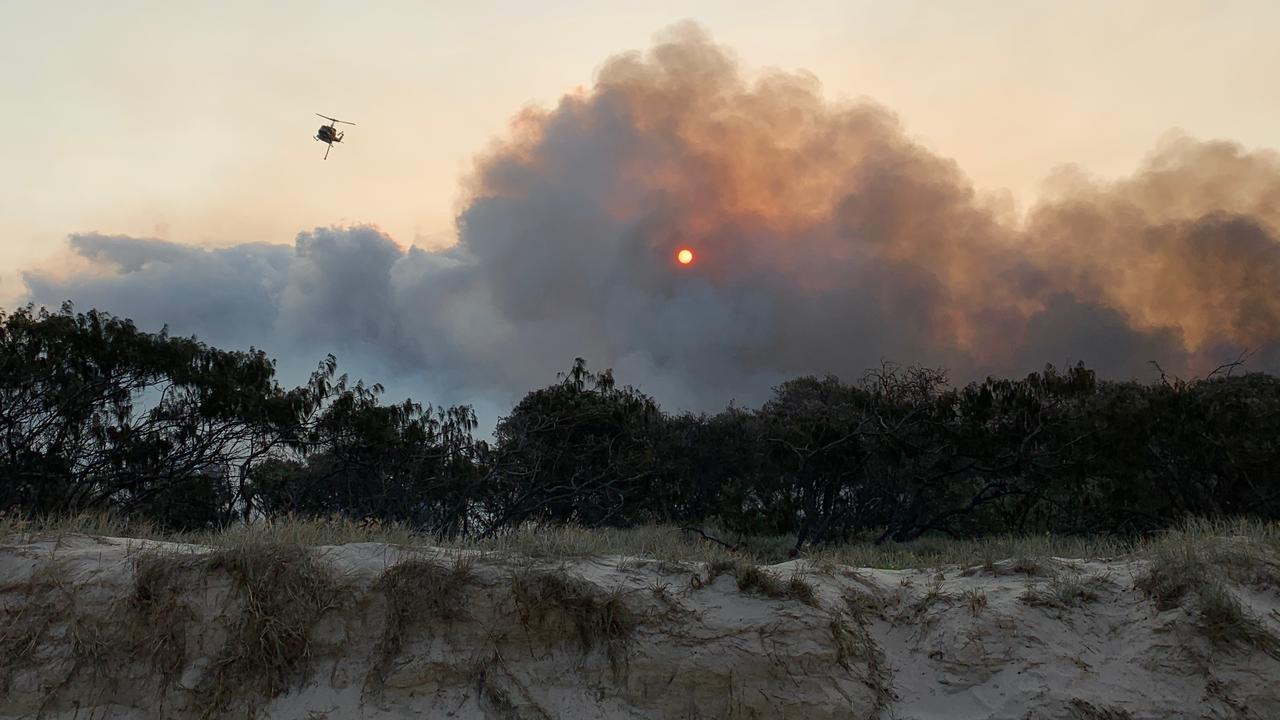 Smoke and flames billow up from behind the sand dunes north of Teewah this afternoon as McDermott Aviation helicopters water bombed a wildfire burning in Cooloola Recreation Area.