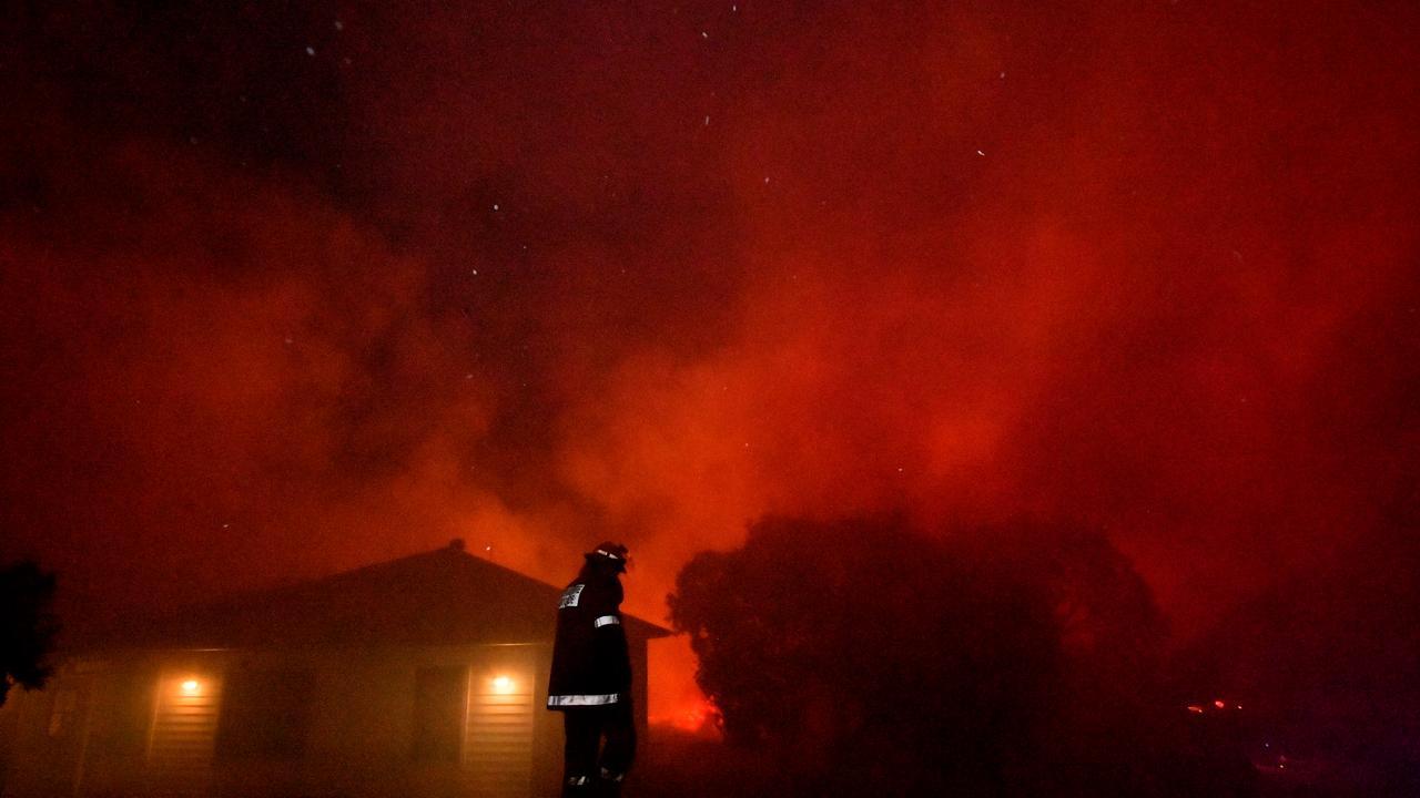 A firefighter keeps watch over homes at Peregian during intense bushfires.Photo: John McCutcheon / Sunshine Coast Daily