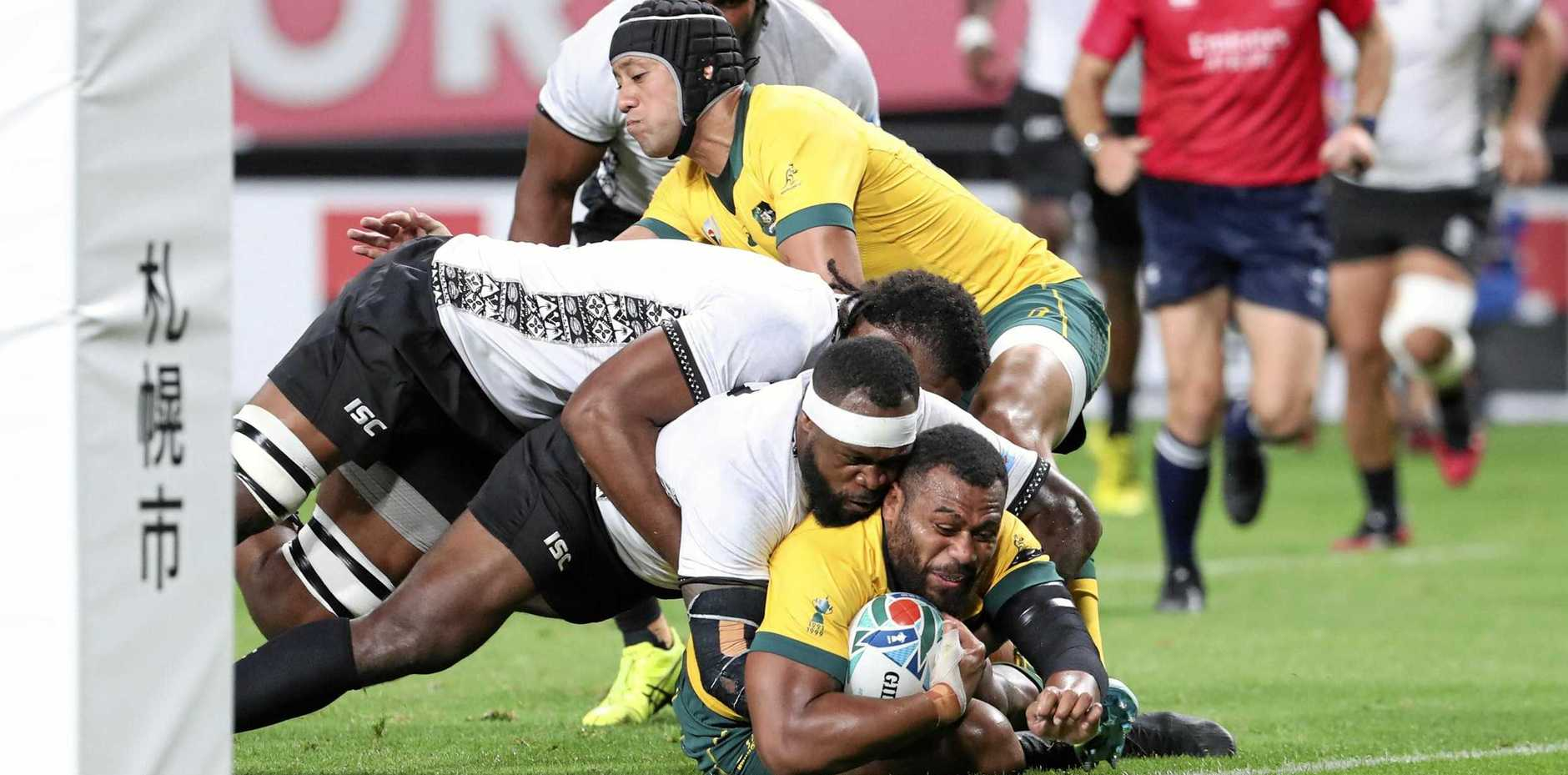 Fiji's Levani Botia struggles to stop Australia's Samu Kerevi from scoring in the first half of their Rugby World Cup opener. Picture: Masaharu Sugimoto/AP