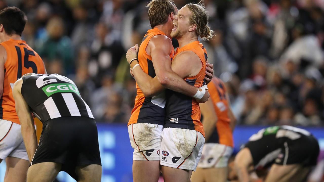 Giants Harrison Himmelberg and Jeremy Finlayson embrace on the final siren as Collingwood players slump in despair. Picture: Michael Klein
