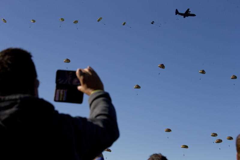 Spectators watch a mass parachute drop at Ginkel Heath, eastern Netherlands, Saturday, Sept. 21, 2019, as part of commemorations marking the 75th anniversary of Operation Market Garden.