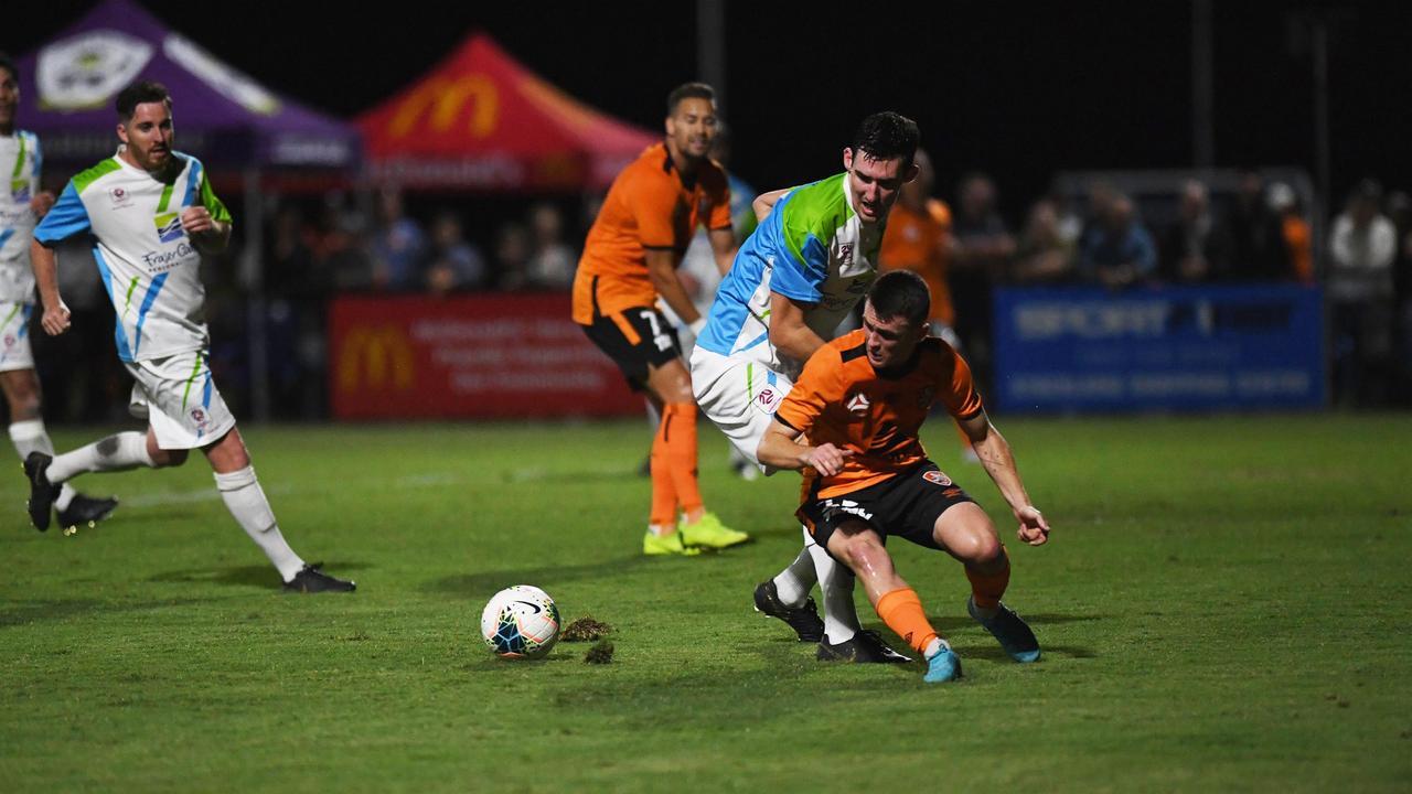 Brisbane Roar (orange) v Wide Bay Select (green) — Joel Haack (Wide Bay) and Dylan Wenzel-Halls (Roar) battle for the ball.