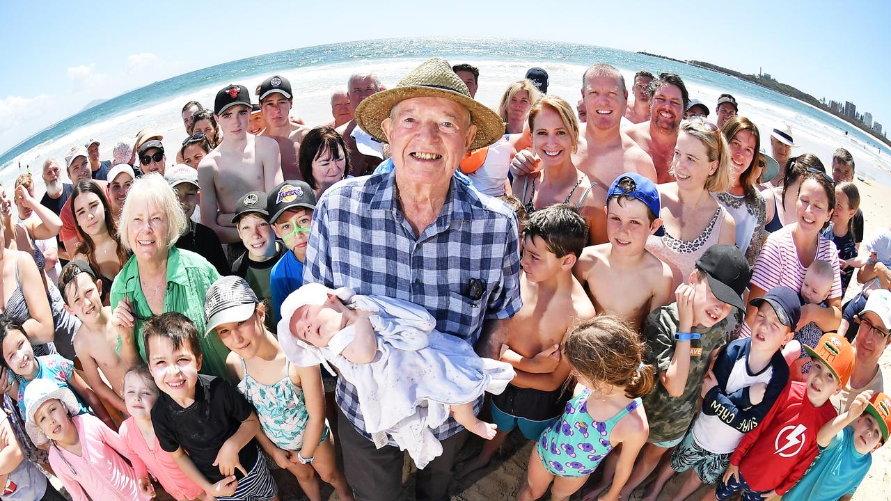 HOLIDAY CREW: Maurice Pitard holds Chloe Bridger among a group of friends who have been holidaying at Mooloolaba since 1996. Photo Patrick Woods / Sunshine Coast Daily.