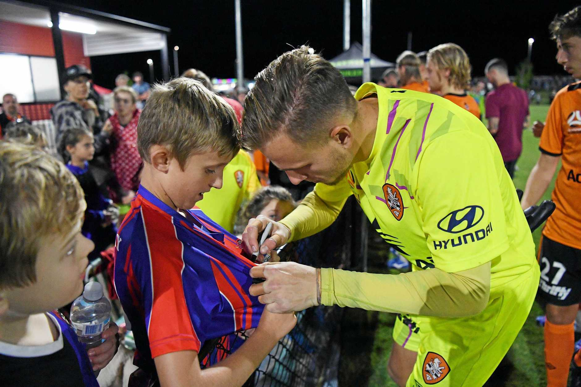 Roar goalkeeper Macklin Freke signing a local Wide Bay Buccaneers player's shirt.