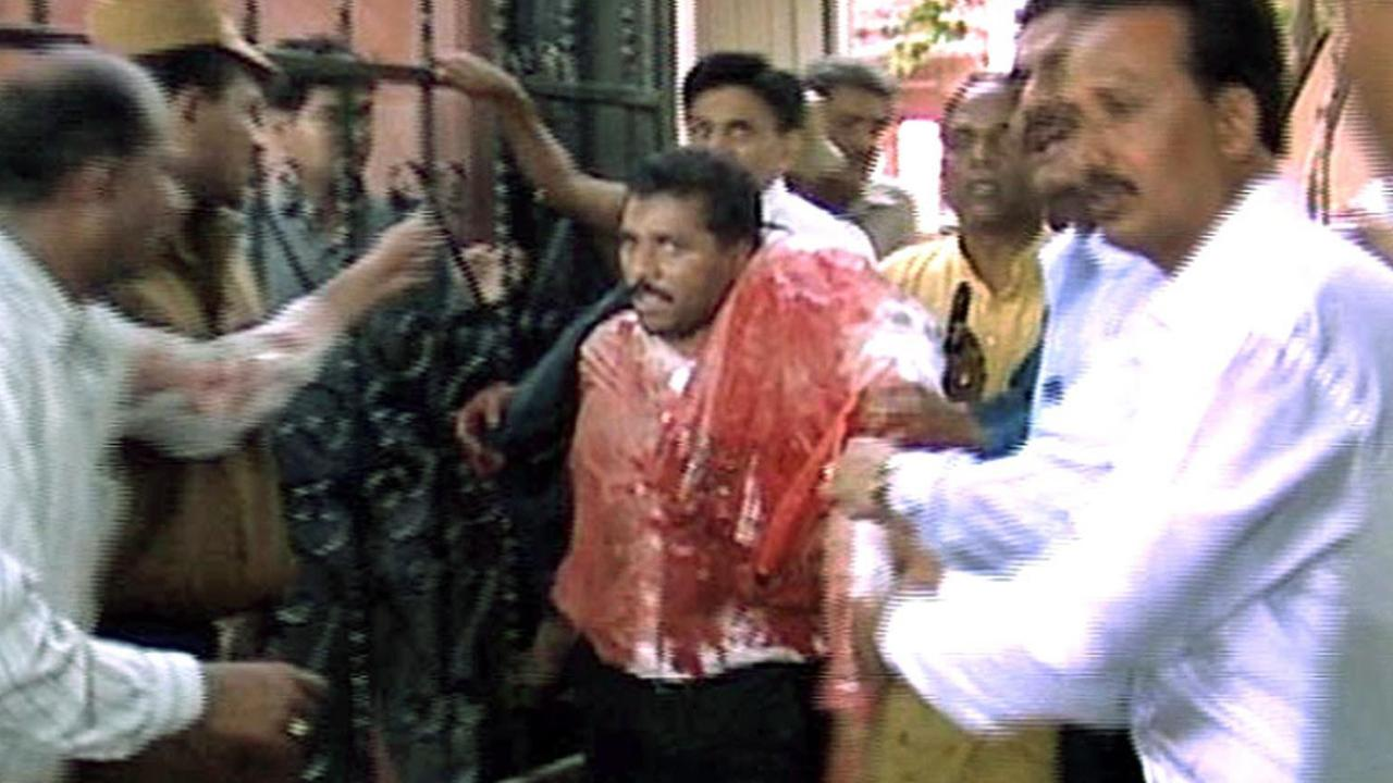 An injured man is helped from a temple in Gandhinagar, after it was attacked by gunmen on this day in 2002.