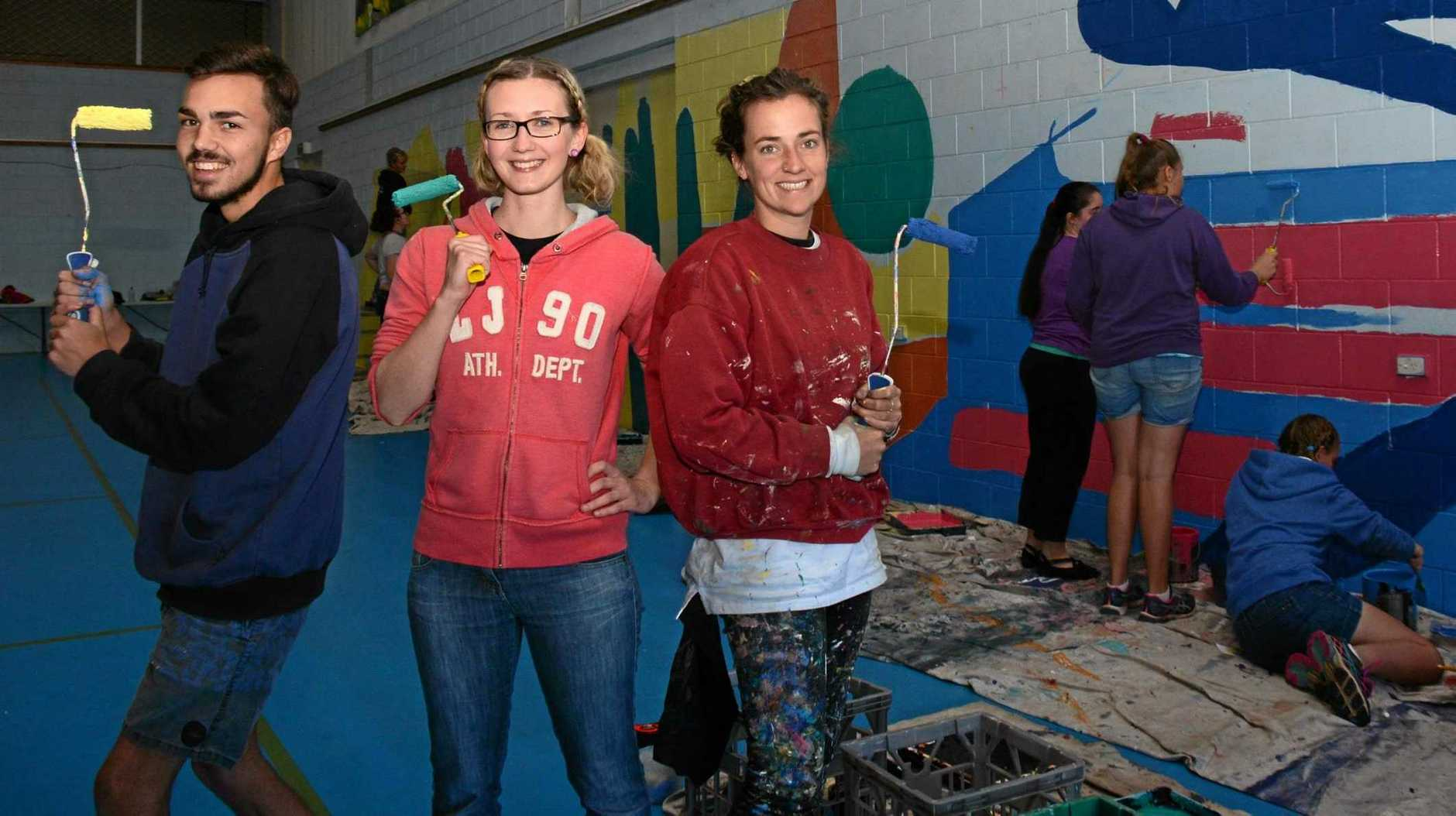 Lead artist Kane Brunjes, project co-ordinator Olivia Everitt and Bronte Naylor help a group of students paint a mural at the Murgon PCYC at a previous art project.