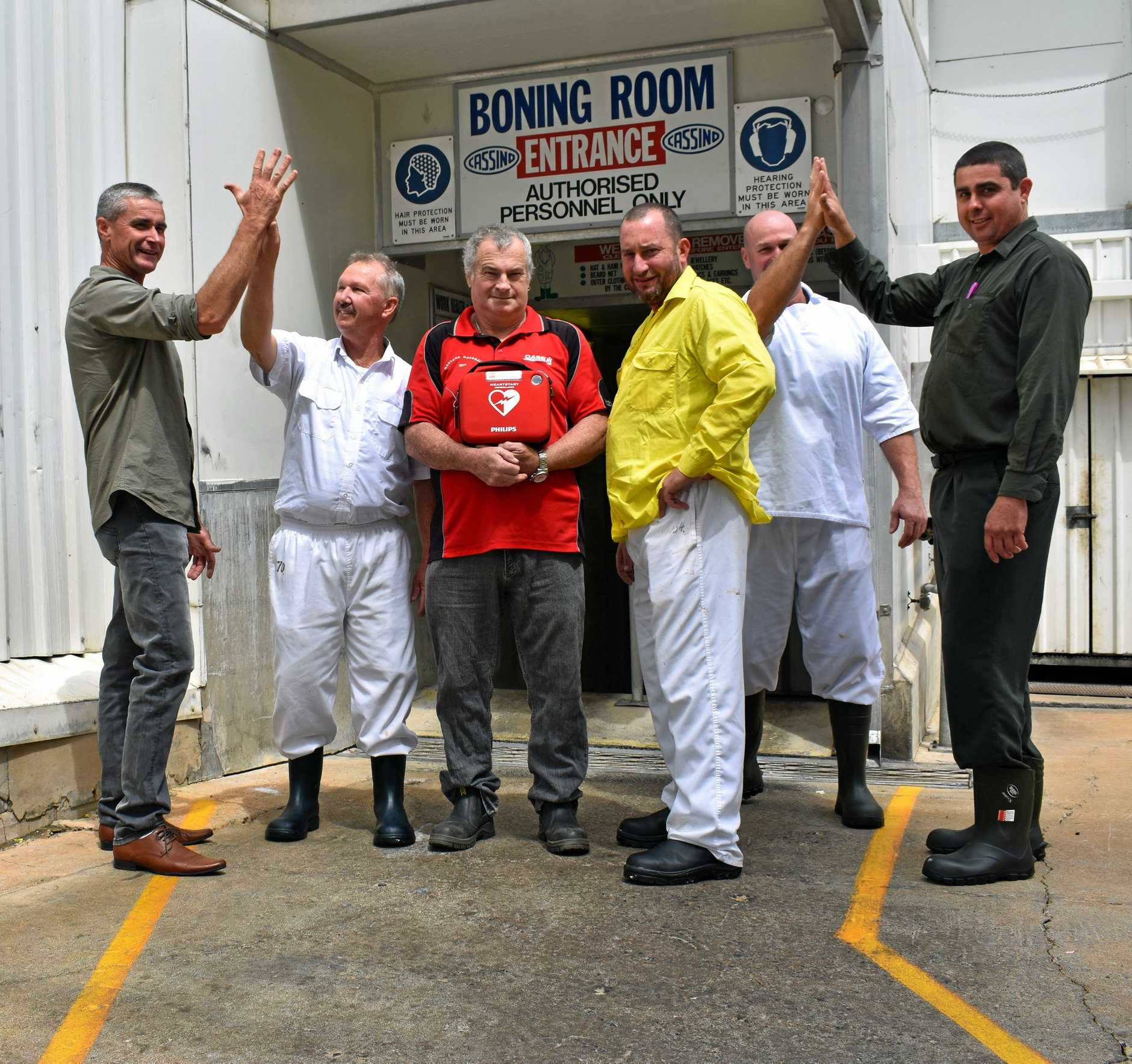Dave Carroll in the centre holding the defibrillator, with the men who saved his life- Darren Grimston, Darrell Schultz, Jason Keep, Luke Murphy and Steve Formaggian outside the boning room at Casino's NCMC.