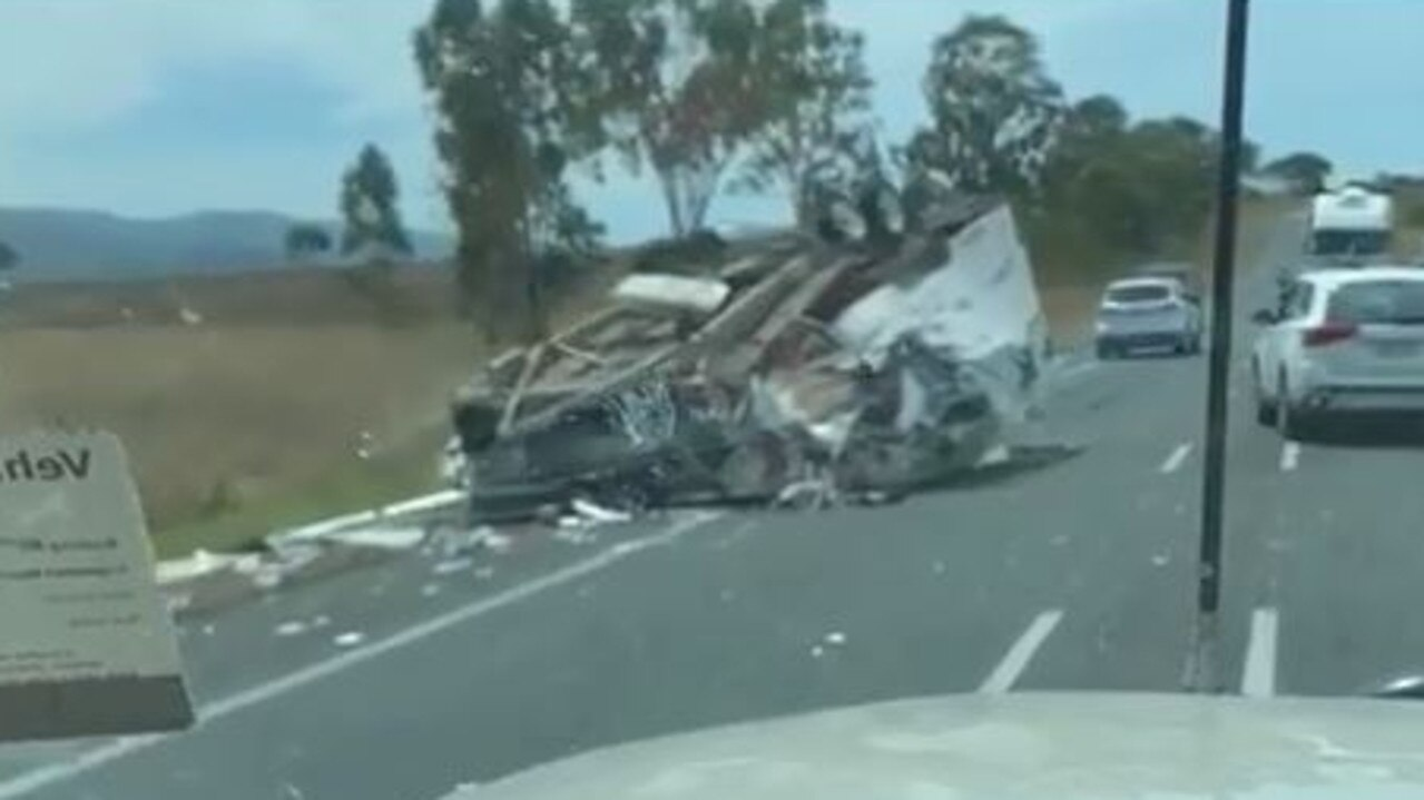 A caravan is in pieces across the Bruce Highway after the car which was towing it rolled.