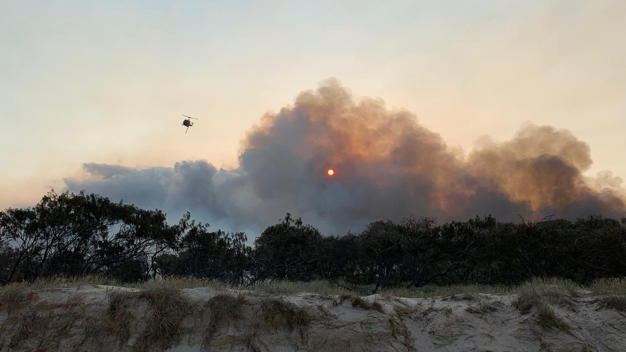 Smoke and flames billow up from behind the sand dunes north of Teewah as McDermott Aviation helicopters water bombed a wildfire burning in Cooloola Recreation Area. Sections of the Noosa north shore will reopen to campers from Friday.