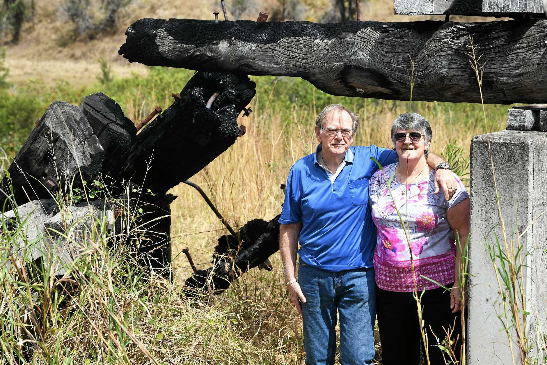 Woolooga residents Vin and Dianne Hollis near the burnt down bridge.