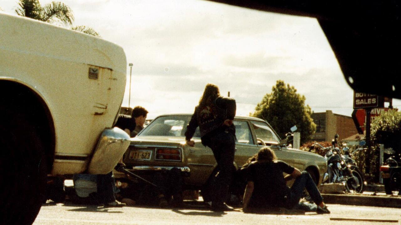 Comanchero bikie gang member Robert Heeney is standing beside the car outside the line of fire at the Milperra Massacre, injured John Hennessey is sitting, Glen Eaves crouches on the left with a shotgun, and Comanchero leader Jock Ross lies injured beneath the car.