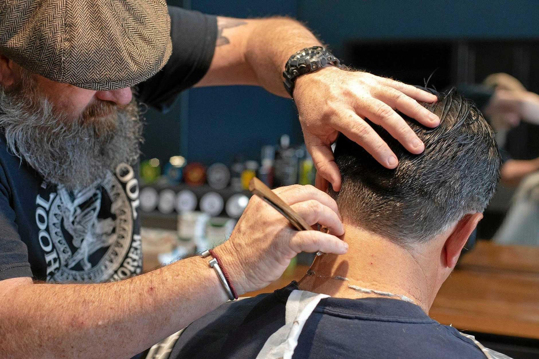 Damian Roche from Houston and Co Barber Shop in Karalee tends to a client.