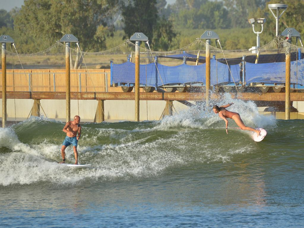 Pro surfers Kelly Slater and Stephanie Gilmore ride a wave at the Kelly Slater Surf Ranch in California. (Photo by Charley Gallay/Getty Images for Breitling)