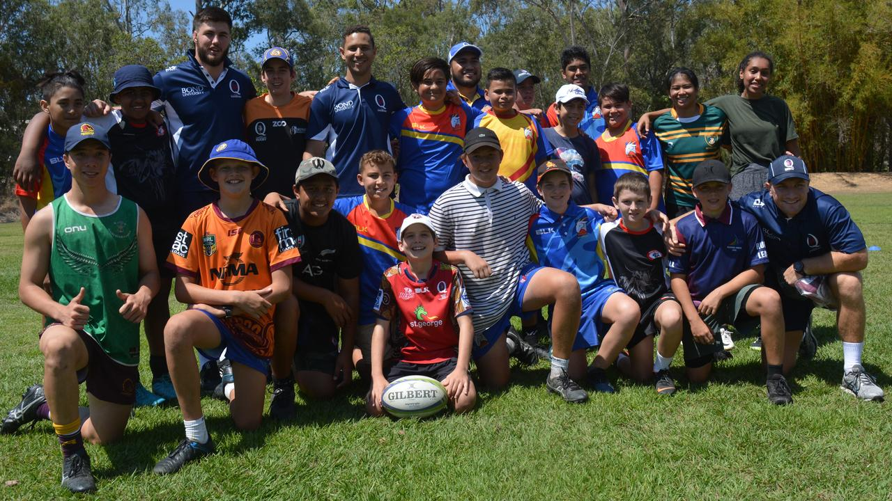 Queensland Country players Liam Wright, Jono Kent, SJ Tamala and James Tuttle with the many youngsters after the junior clinic yesterday
