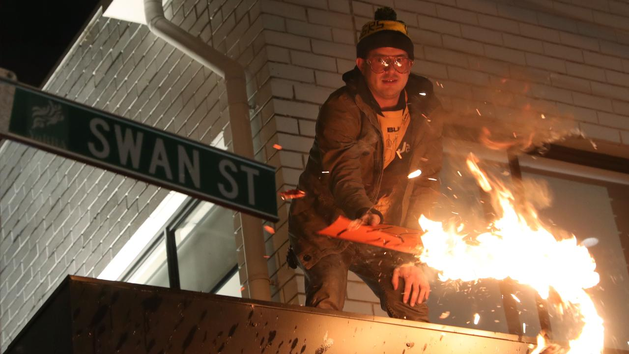 A man burns a sign in Swan Street before being arrested.