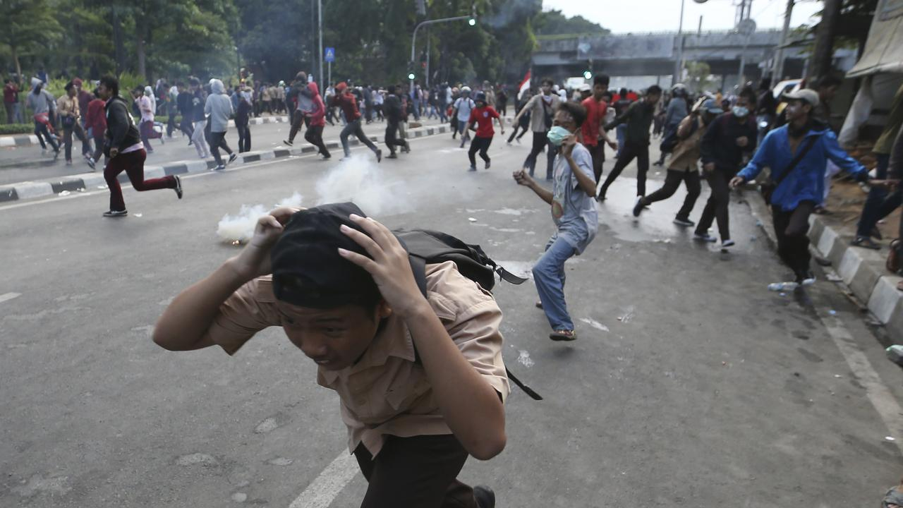 Indonesian riot police shot multiple rounds of tear gas at thousands of stone-throwing students marching towards parliament on Wednesday. Picture: AP Photo/Achmad Ibrahim