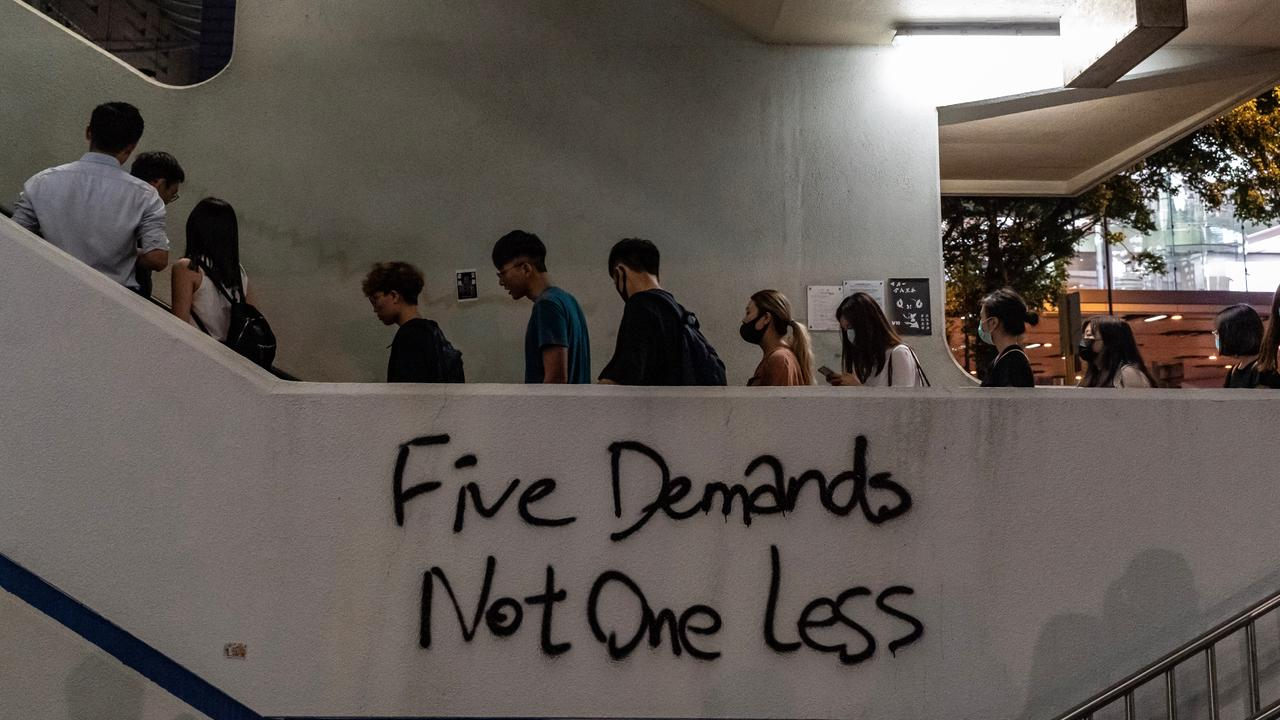 """A """"Five Demands Not One Less"""" graffiti sign seen as pedestrians ride an escalator. Picture: Anthony Kwan/Getty Images"""