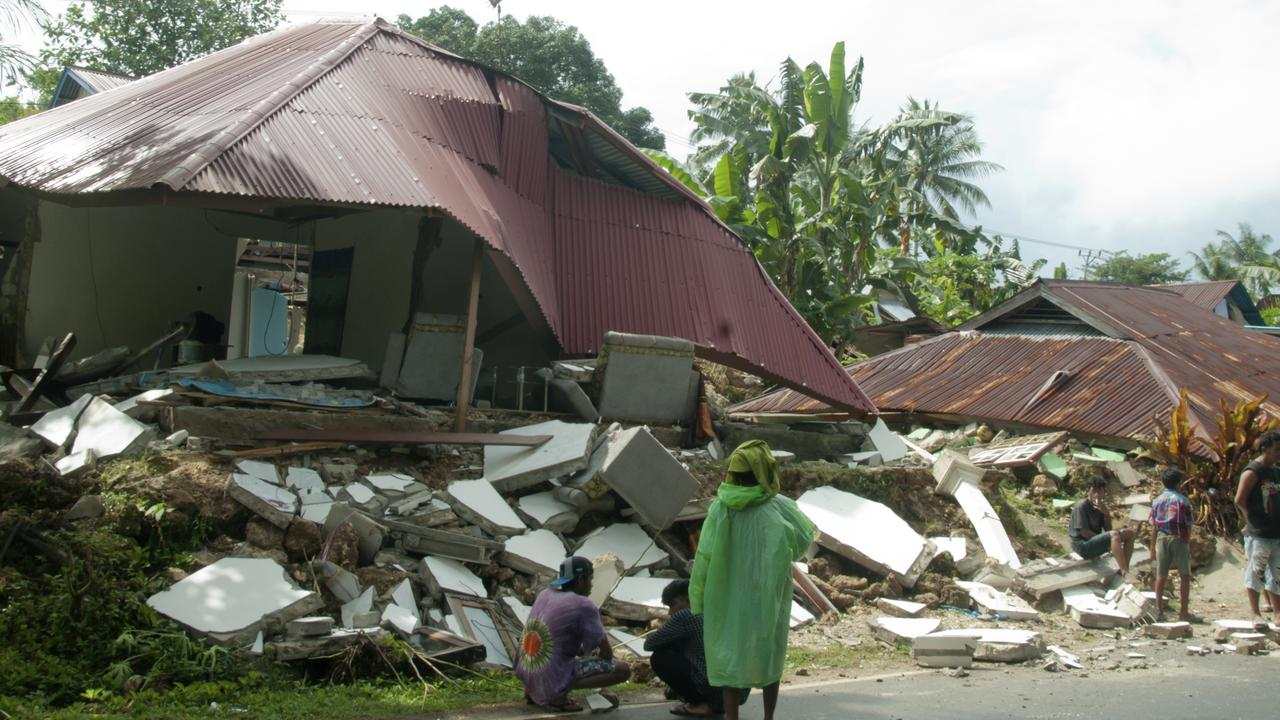 Residents stand near earthquake-damaged houses in Ambon. Picture: Tiara Salampessy/AP