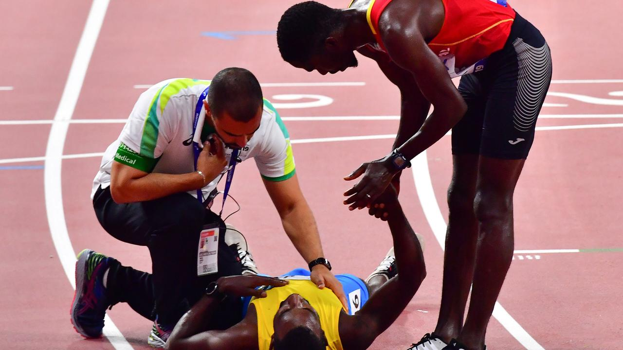 Jonathan Busby collapses after crossing the finish line in the 5000m heats.